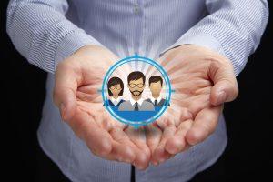 Kundenservice B2B: der Kunde im Mittelpunkt: Icons von drei verschiedenen Köpfen, die in zwei Händen gehalten werden